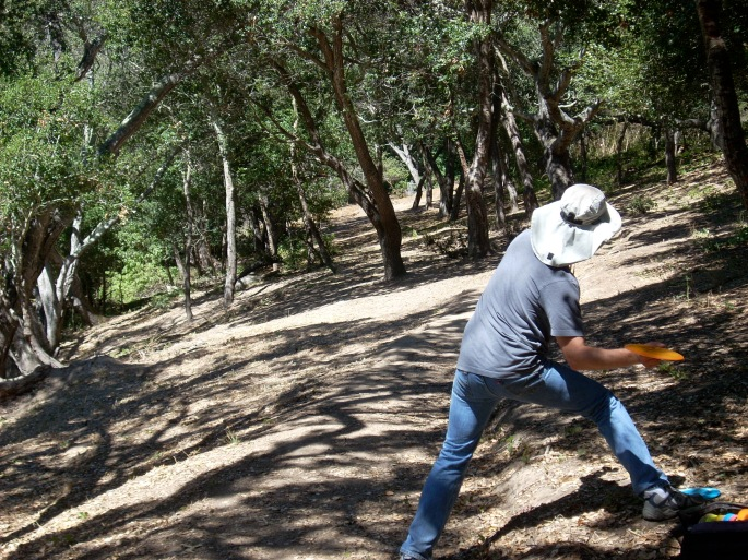 As shown on this shot from the fairway of hole #3 at Pinto Lake DGC in Watsonville, CA (site of the 2011 PDGA World Championships), disc golf can be played on severe slopes and any type of ground cover- in this case bare dirt.