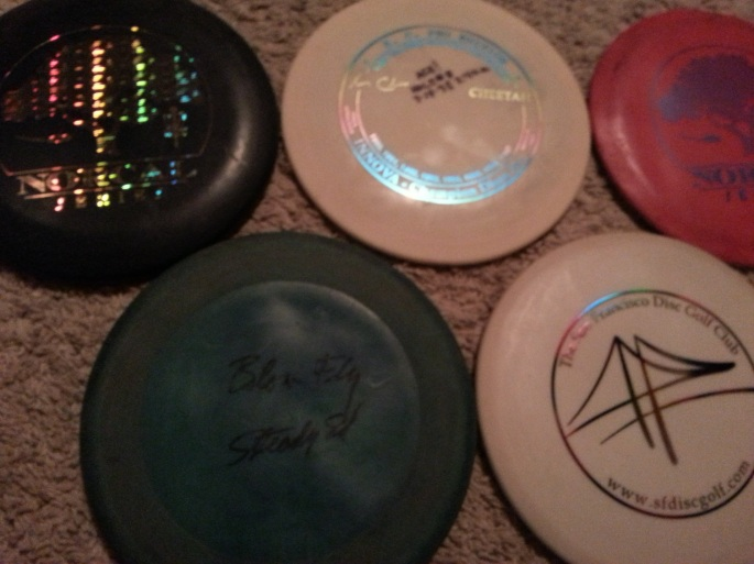 The author collects only discs with personal significance. Among this group are his first ace, most memorable ace, a disc to commemorate the opening of the first course in S.F., a NorCal 'Hotshot' disc awarded for the low round in a tour event, and a prototype DGA Blowfly signed and given to him by Steady Ed Headrick. Blurry photo by Jack Trageser