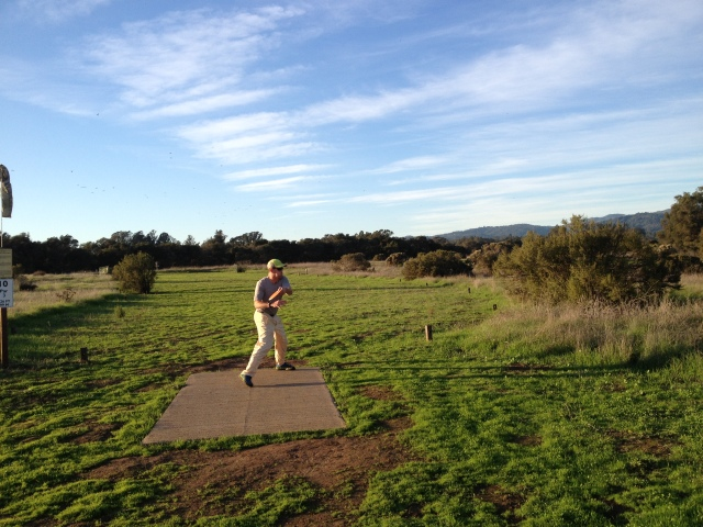 Hole 10 at Pinto Lake CDGC has OB along both sides of the fairway. The player pictured intends to release an overstable O-Lace on a sharp anyhyzer line aimed at the right side so it will turn over toward the basket then straighten out as it finishes.
